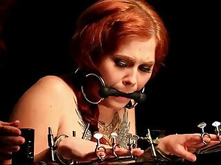 Gagged redhead teen babe in bondage device gets spanked
